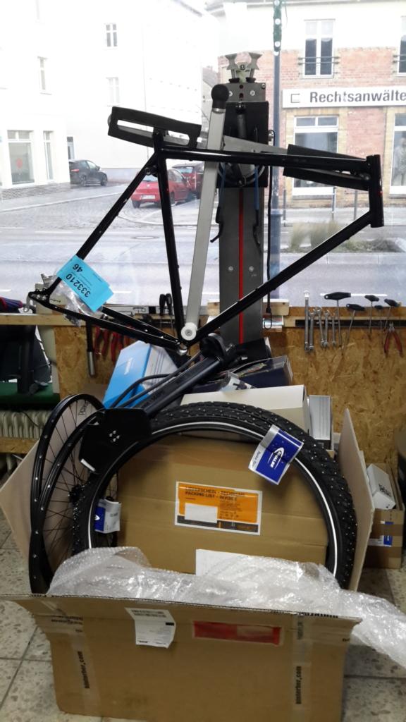 Fahrradrahmen am Montageständer, davor ein großer Karton übervoll mit Fahrradteile