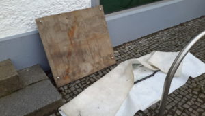 Holzplatte und eingewickelte Scheibenreste draußen abgelegt