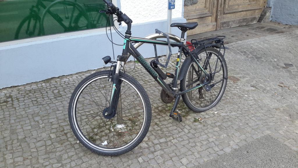 Fahrrad am Anlehnbügel vor dem Laden angeschlossen
